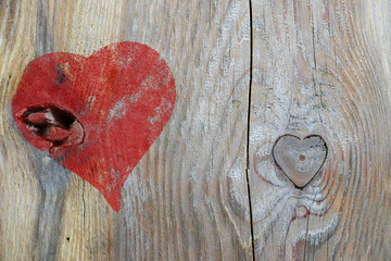 red heart painted on wood and knothole in heart shape, love back
