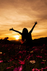 happiness woman enjoying beautiful sunset in flower garden