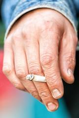 Male hand holding a cigarette.