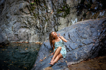 beautiful girl posing in dress at the waterfall