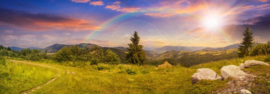 boulders on hillside meadow in mountain at sunset with rainbow