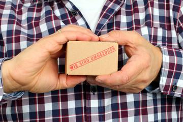"""kleiner Umzugskarton """" wir ziehen um"""" in Hand"""