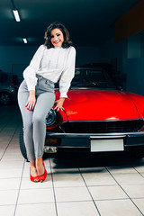 Beautiful young woman posing on a red vintage car