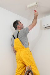 Worker painting ceiling in room with paint roller