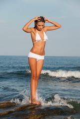 Beautiful young model posing on rocks in sea water
