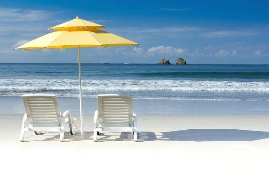 Yellow beach umbrella on white beach with blue sky and ocean