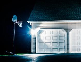 Garage and basketball hoop at night.