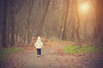 Little girl in the autumn forest