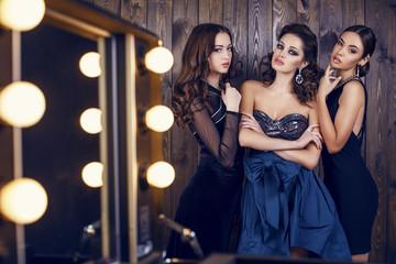 beautiful women  in luxurious dresses posing at studio
