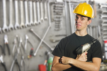 Worker holding electric drill and wearing hard hat