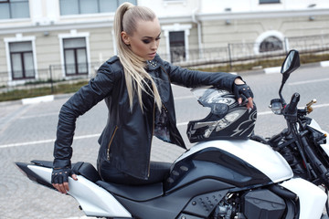 girl with blond hair in leather jacket,posing on motorbike