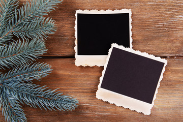 Blank photo frames and fir tree on wooden table background