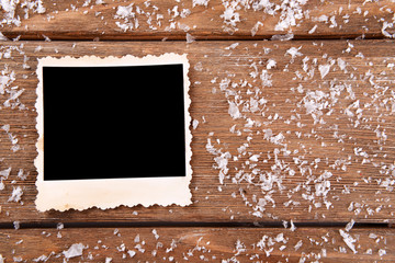 Blank photo frame and snowflakes on wooden table background