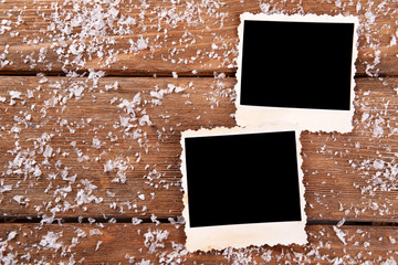 Blank photo frames and snowflakes on wooden table background