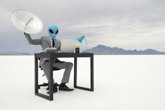 Alien Businessman Sitting at Desk with Satellite Dish