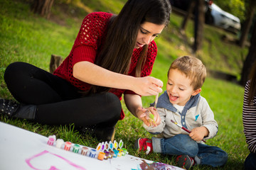 Mom painting her son´s hand in the park
