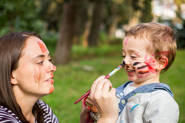 Happy mother painting her child´s face in the park