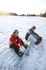 눈밭에서 스케이트보드 타는 커플