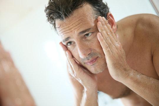 Handsome man rinsing face after shaving