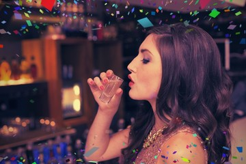 Composite image of pretty brunette drinking a shot
