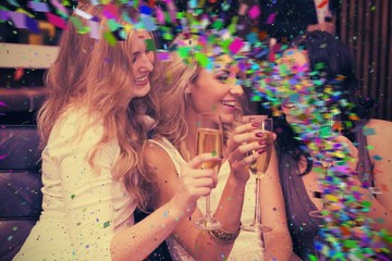 Composite image of happy friends drinking champagne together