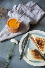 toasted sandwich with orange carrot smoothie on table
