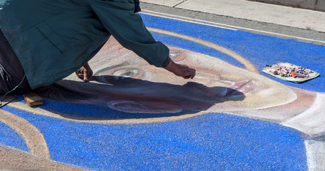 artist paints with colorful chalks on the street image of saints