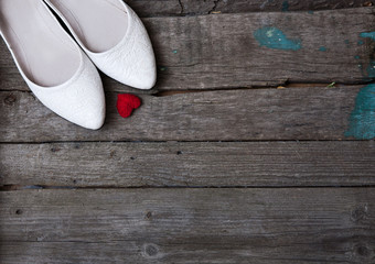 wedding shoes and red heart on wood background