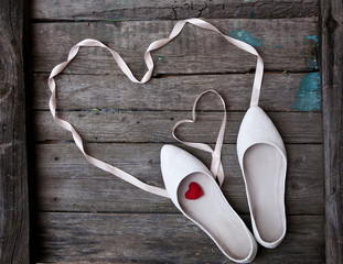 wedding shoes and ribbon in the form of heart on wood background