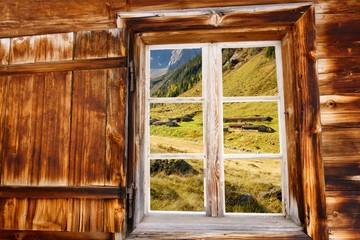 herbstliche Almlandschaft im Holzfenster