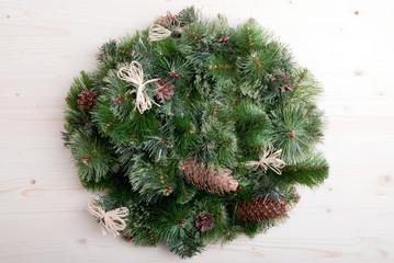 Christmas wreath of pine needles with cones on light board