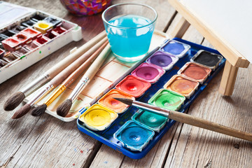 Box of watercolor paints, art brushes, glass of water and easel