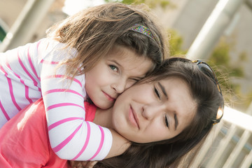 Younger sister hug and wishes her older sister, portrait