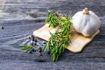 rosemary branch and spices on wooden table