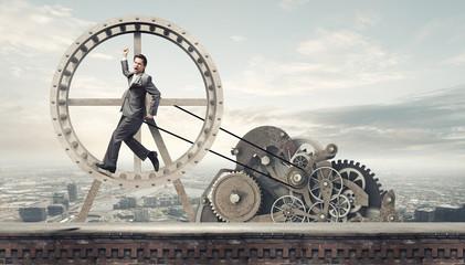 Businessman in wheel Wall mural