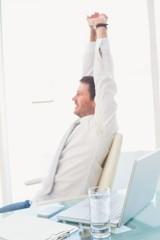 Smiling businessman stretching at desk
