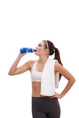 Fit brunette drinking from sports bottle