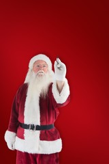 Composite image of santa writes something with a pen