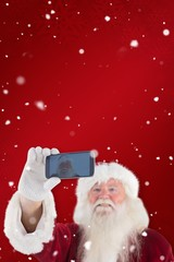 Composite image of santa taking a selfie on phone