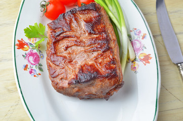 Roast beef  and vegetables on a plate on a wooden table