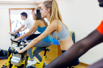 Young people with fitness bycicles in the gym.