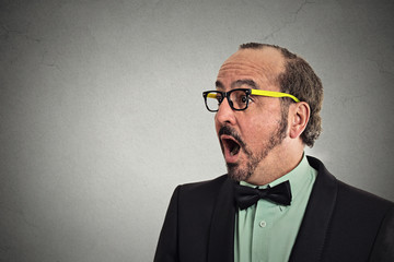 Side profile headshot surprise astonished man grey background