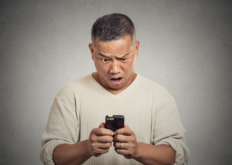 surprised shocked man unhappy by what he sees on cellular phone