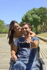 Man in wheelchair and girlfriend taking a selfie