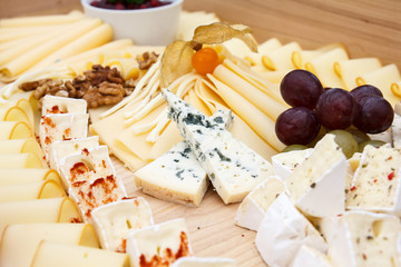 Mixed cheeses on light wooden board.