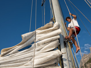 Fototapete - young man working on mast of sailing ship
