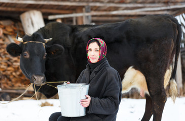 woman with bucket for milking cows in  winter