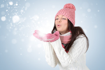 Attractive young woman blowing snow. Girl in warm winter clothes
