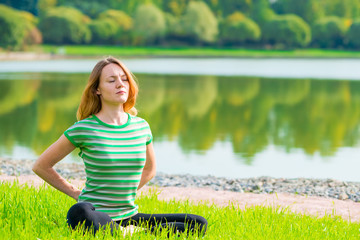 Concentrated woman doing yoga on the grass