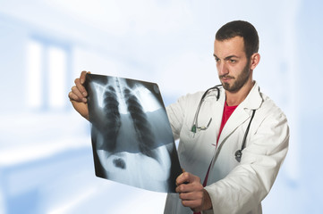 male doctor looking at the x-ray picture of lungs